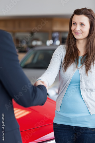 Woman shaking hand to a dealer