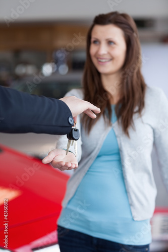 Brunette receiving car keys in his hand