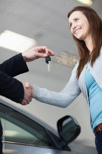 Woman receiving car keys while shaking hand