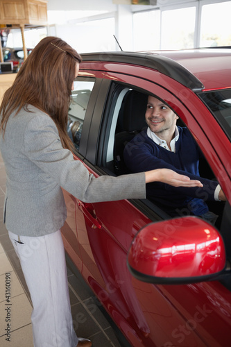 Businesswoman presenting the car to a client