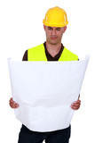 Confused tradesman looking at a technical drawing poster