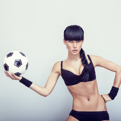 Portrait of a hot young woman holding a soccerball