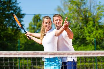 Tennislehrer lehrt Frau Tennis zu spielen
