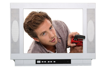 young man with pliers behind a television screen