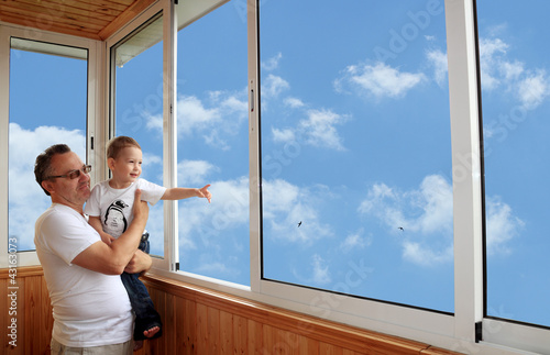 Grandson and grandfather standing on balcony and looking at the