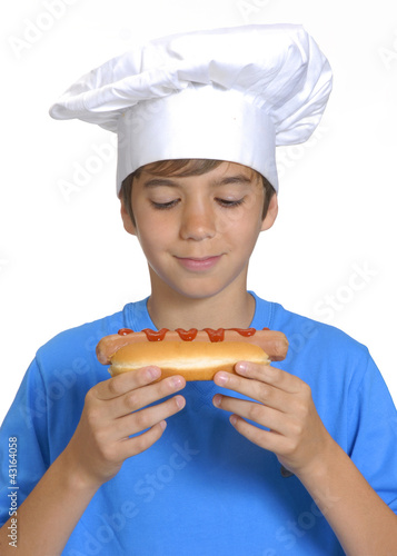 Niño chef sujetando un hotdog,comiendo perro caliente.