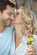 Woman with wild flowers kissing man