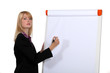 Blond businesswoman about to write on white-board
