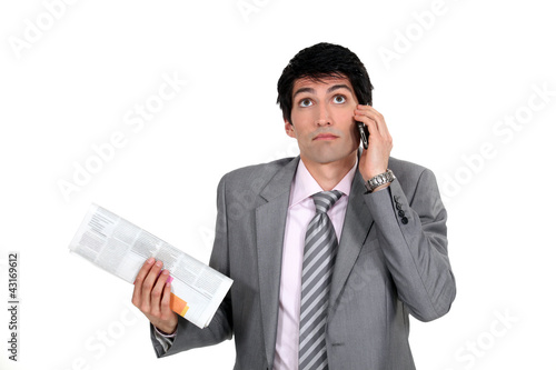 Smart man on the phone holding a newspaper