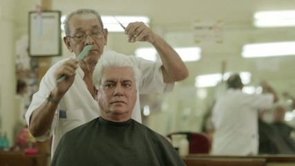 Male beauty, old barber cutting hair to client in barber shop