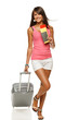 Full length of female in casual walking with travel bag