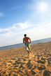 sporty young man running on beach