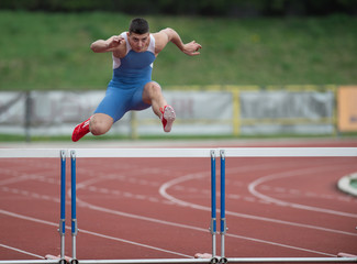 Professional sprinter jumping over a hurdle