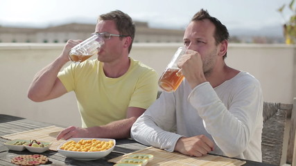 Two happy friends drinking beer, outdoors