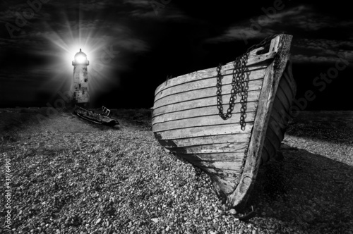 boat on beach lit by the beam of lighthouse