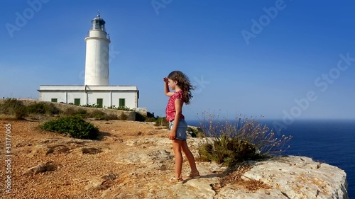 beautiful little girl greeting in mediterranean lighthouse sea