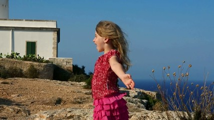 happy little blond girl feeling wind in high cliff  sea