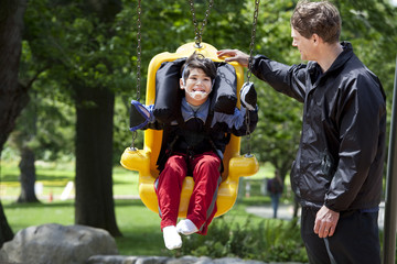 Father pushing disabled boy in special needs swing
