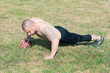 Shirtless american football player doing push-ups with ball