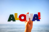 Female's hand holding colorful word 'Aloha'