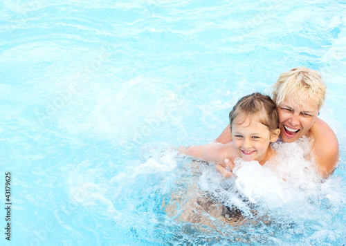 woman and  girl swimming in the pool