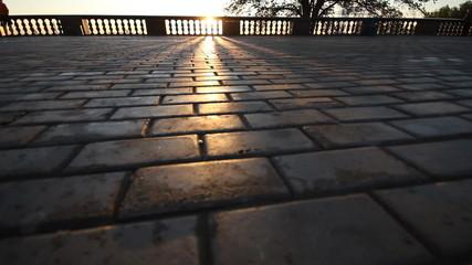 rays of sun over parapet on tile sidewalk