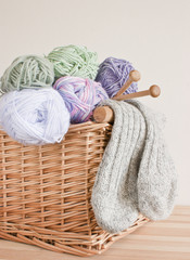 Basket with wool, knitting needles and socks.