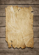 Old paper sheet nailed to a grunge wooden background with copy s