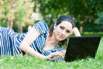 Closeup of a college student using her laptop outdoors at campus