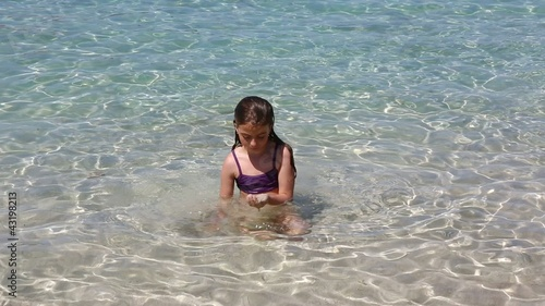 beautiful little girl playing in ibiza beach on vacation