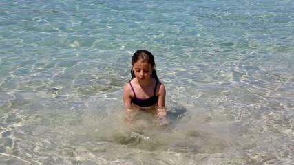 beautiful little girl playing in ibiza beach on vacation