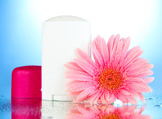 deodorant with flower on blue background