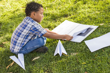Mixed Race Boy Learning How to Fold Paper Airplanes