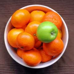 single Green apple in a bowl full of oranges