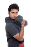 Indian young man curling a dumbbell over a white background.