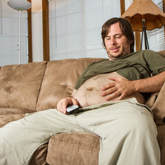 Heavy set man on the couch admiring his stomach