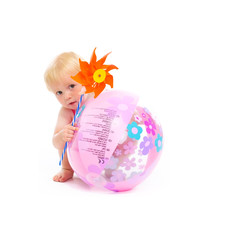 Baby in swimsuit with pinwheel hiding behind beach ball