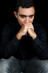 Thoughtful hispanic man with a sad expression isolated on black