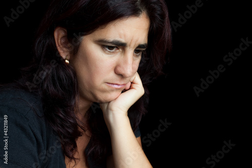 Portrait of a sad and depressed hispanic woman isolated on black
