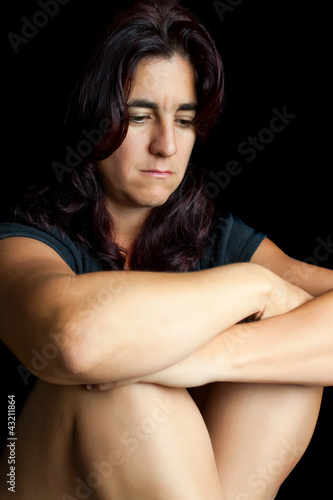 Sad and worried hispanic woman sitting isolated on black