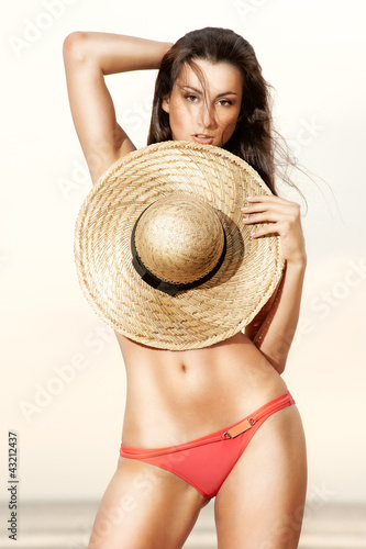 Georgian girl on the beach with a straw hat