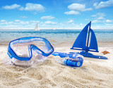 Fototapety Goggles and toy sailboat in sand