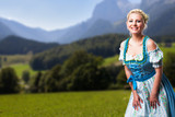 junge blonde Frau im Dirndl vor Alpenlandschaft