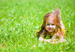 A smiling girl is lying on the meadow