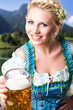 junge blonde Frau im Dirndl mit Masskrug vor Alpenhintergrund