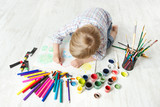 Child drawing picture with crayon  in album using a lot of paint