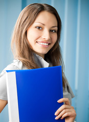 Young cheerful business woman with blue folder