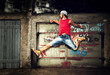 Young man jumping, dancing on grunge wall
