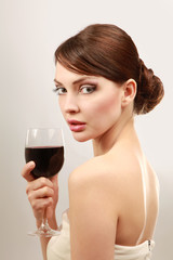 Beautiful brunet girl drinking red wine isolated