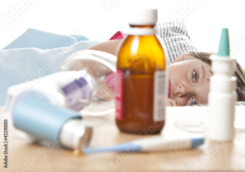 ill little girl and her drugs, inhaler and thermometer